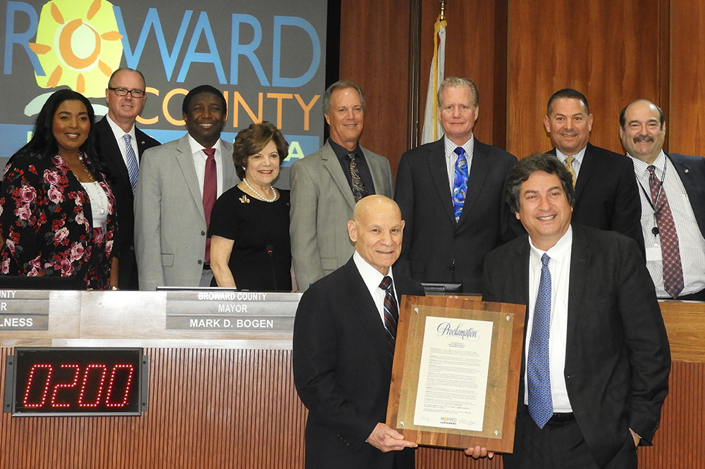 Mayor Bogen presenting State Attorney Mike Satz with a proclamation, alongside the Broward County Board of County Commissioners.