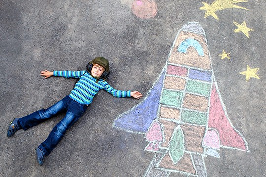 boy next to chalk drawing of rocket