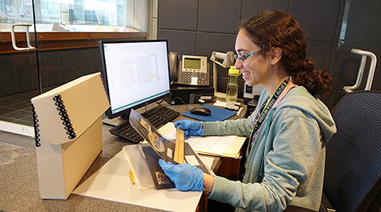 woman measuring an item from the historical archives