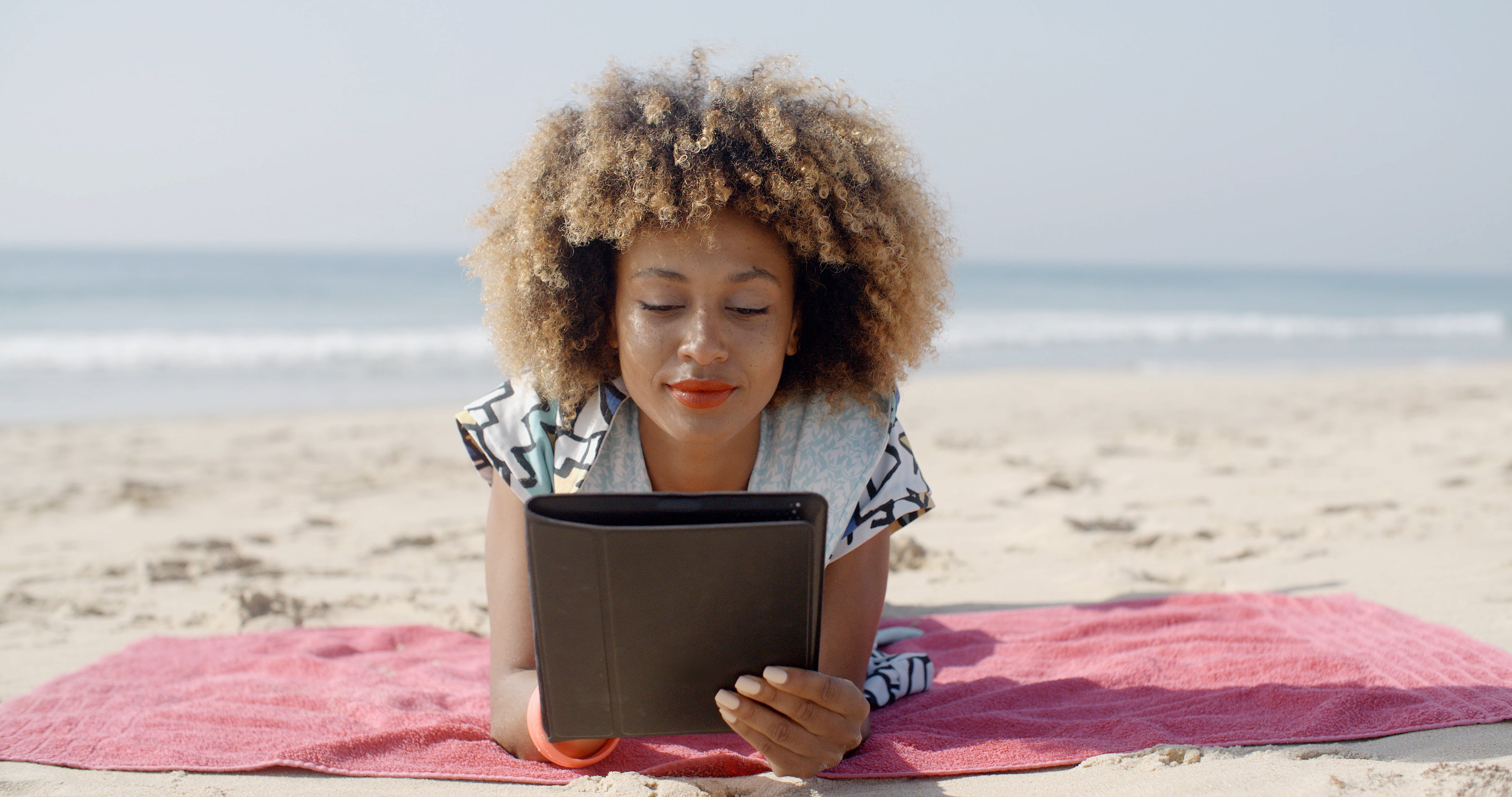 young woman lying on beach reading a digital tablet