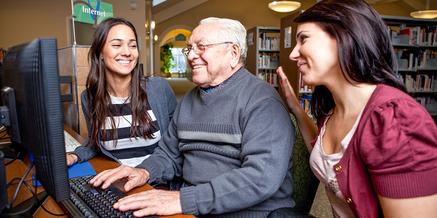 young women working with senior man on a computer