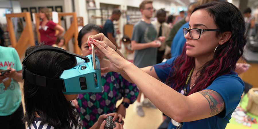 librarian fitting child with virtual reality glasses