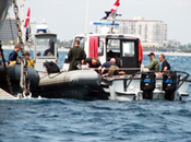 U.S. military divers boarding a boat to take them back to shore after completing a days work.