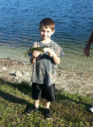 Boy holding up fish